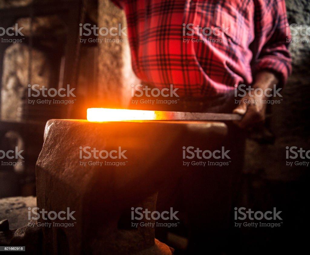 Hot Iron on Anvil in Blacksmith Shop stock photo