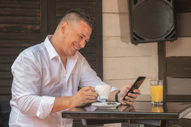 Hot Italian businessman sitting in restaurant and drinks his coffee while he smiling stock photo