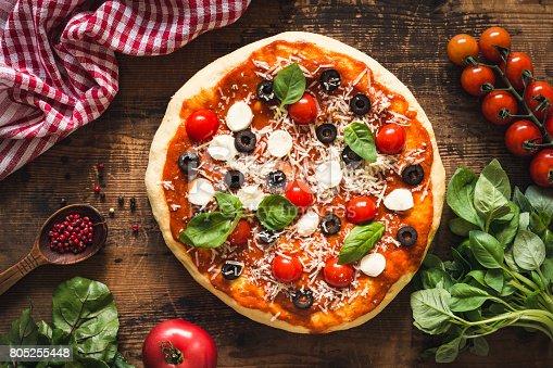 istock Hot italian pizza on wooden table 805255448