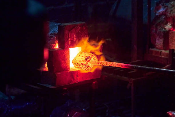 Hot item is inserted into the blacksmith's forge from which the tongues of flame. Concept: blacksmithing, forge Hot item is inserted into the blacksmith's forge from which the tongues of flame. Concept: blacksmithing, forge anvil stock pictures, royalty-free photos & images
