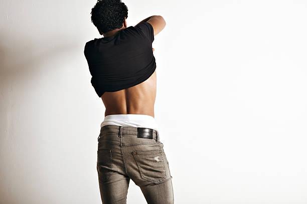 Hot latino young man taking off his t-shirt stock photo