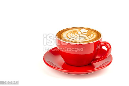 istock Hot latte coffee with latte art in a bright red cup and saucer isolated on white background with clipping path inside. 1047058672