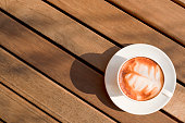 hot latte coffee with latte art palm leaf-shaped in a classic white coffee cup set flat lay top view with beautiful abstract shadow on the vintage wooden table pattern background texture