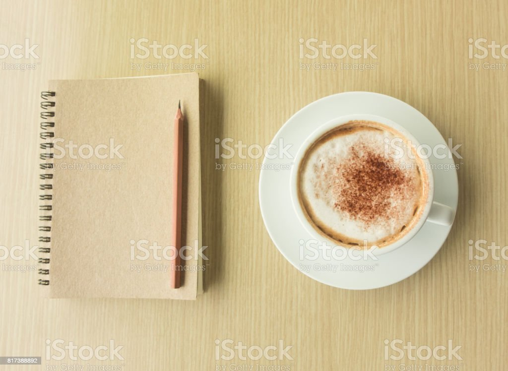 Hot latte in white cup, pencil and notebook on wood table in top of view stock photo