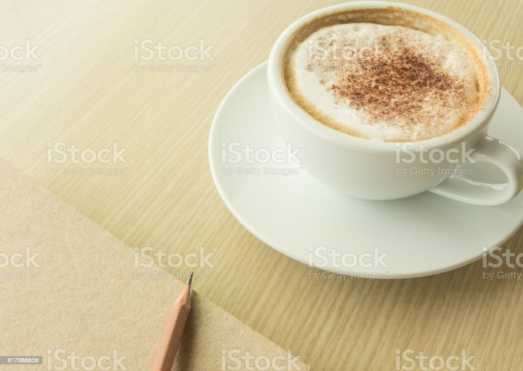 Hot latte in white cup, pencil and notebook on wood table. stock photo