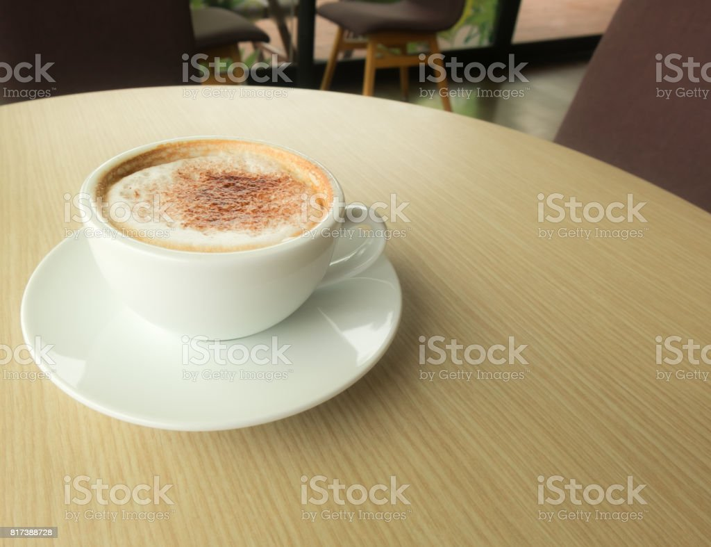 Hot latte in white cup put on wood table in coffee cafe. stock photo