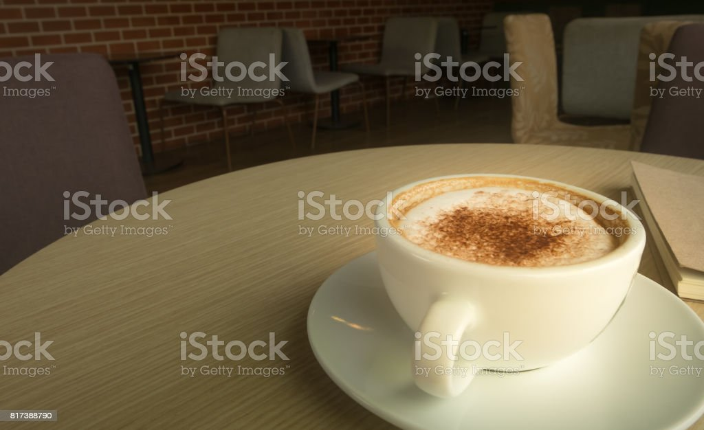 Hot latte in white cup put on wood table in dark room of coffee cafe. stock photo