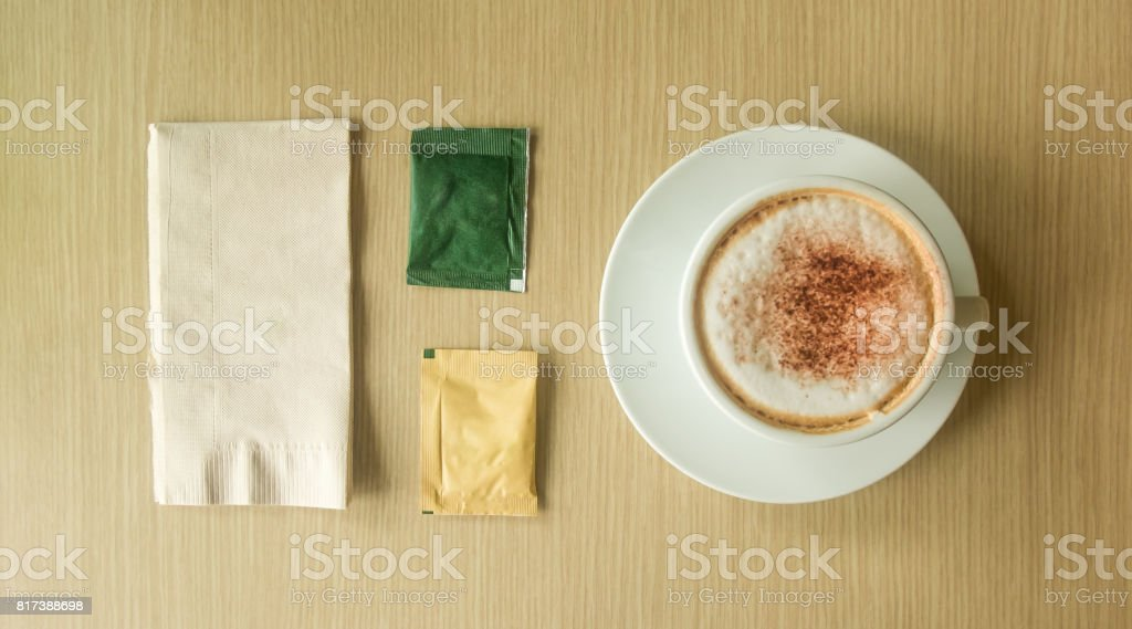 Hot latte in white cup, sugar packets and tissue paper on wood table. stock photo