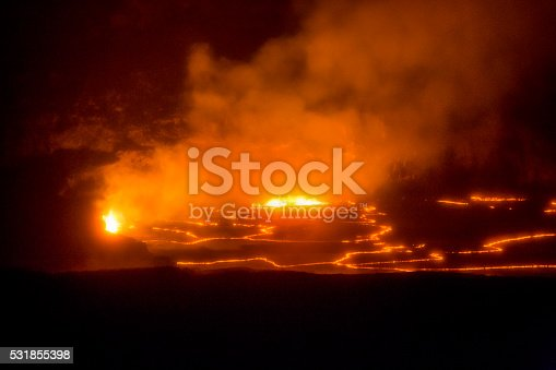 Orange molten magma erupts and churns night inside Hawaii Island's Kilauea volcano. The Lava lake is glowing orange and illuminating the caldera. A cloud of volcanic gasses are billowing upward. The image is horizontal and mostly dark except for the glowing areas (stock image)