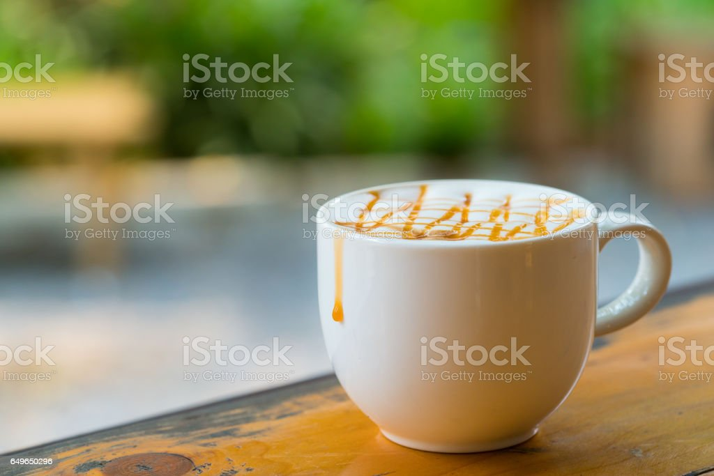 Hot Macchiato coffee with caramel in white cup on wood table stock photo