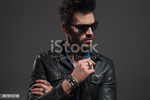 istock hot man in leather jacket and sunglasses looking to side 907610746