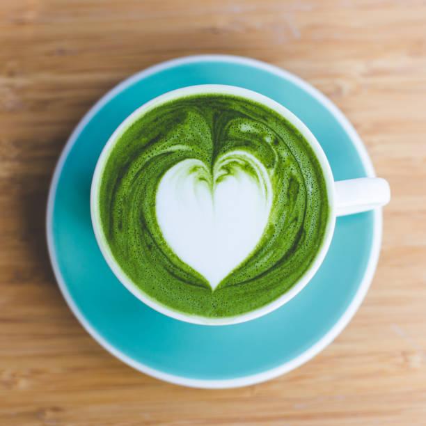 heißen matcha grüntee mit herz form latte art in grün cup am holztisch. liebe konzeption. - grüner tee koffein stock-fotos und bilder
