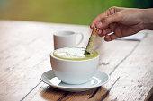 白いセラミックカップのホット抹茶ラテまたは緑茶、シナモンで若い女性の手でソパライザーを着て