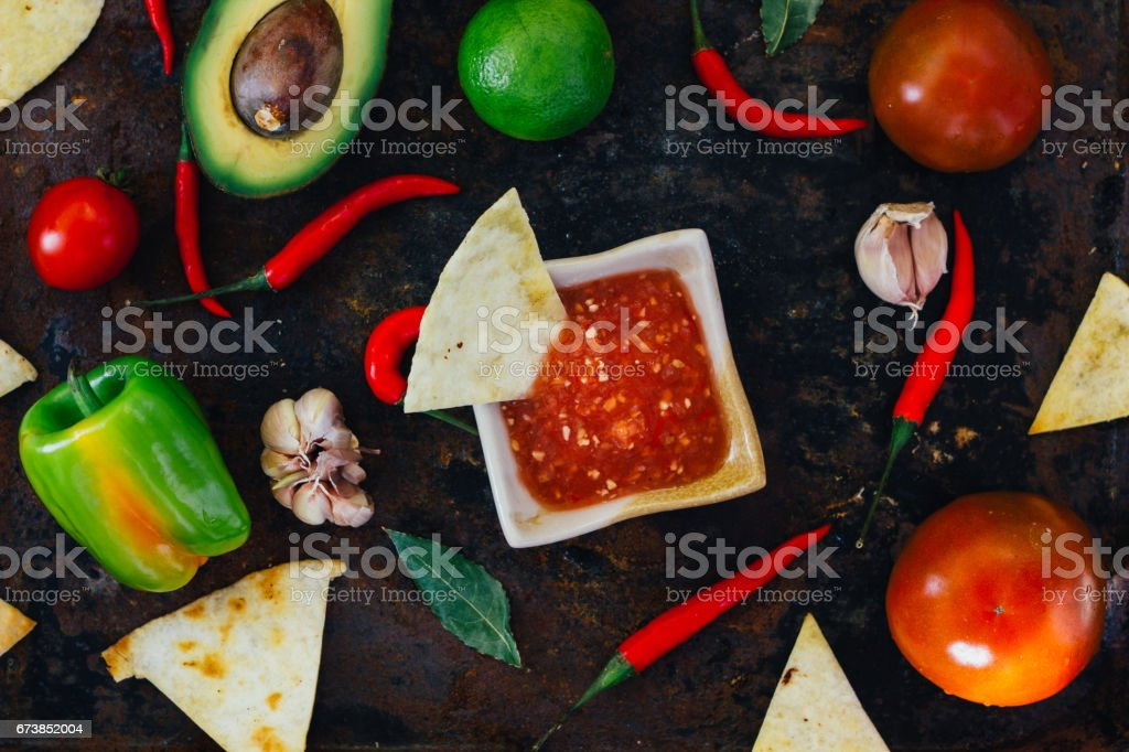 Hot mexican salsa whith the nacho chips surrounded by ingredients - tomatoes, chili peppers, lime. photo libre de droits