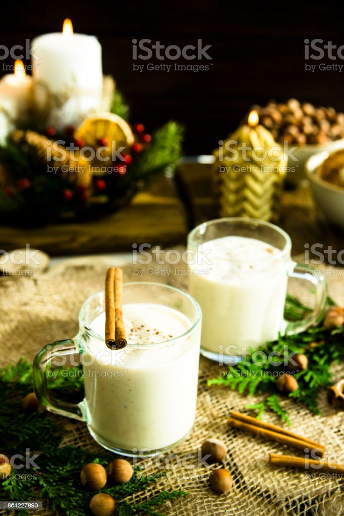 hot milk alcoholic drink   Egg-nog next to the Christmas candle and candles royalty-free stock photo