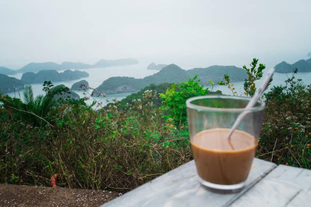 Heißer Milchkaffee im vietnamesischen Stil. Frühstück mit einem schönen Blick auf die Felsen, die aus dem Wasser ins Meer ragen. Halong Bay in Nordvietnam, Kopierraum – Foto