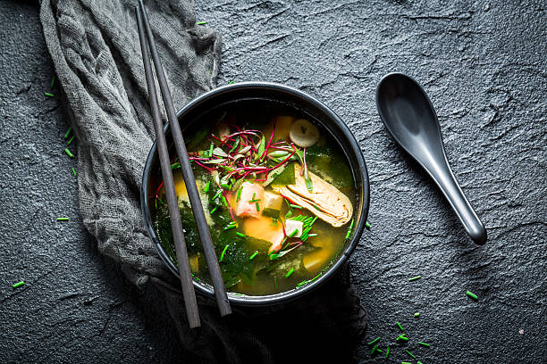Hot miso soup with salmon in black bowl stock photo