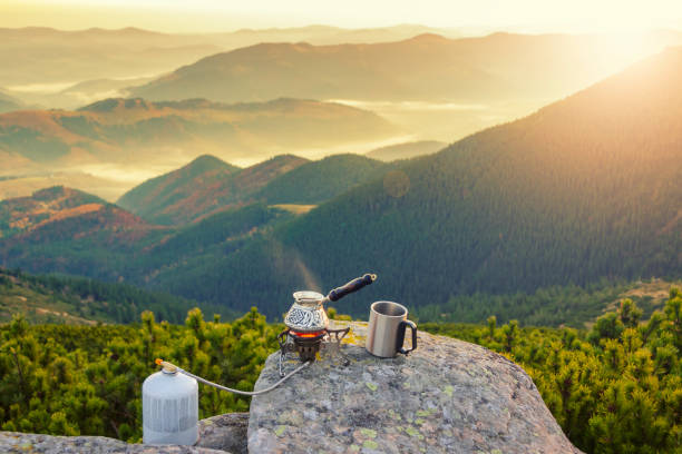 Hot morning coffee high in the mountains. Preparing coffee with gas camping stove. Morning outdoors