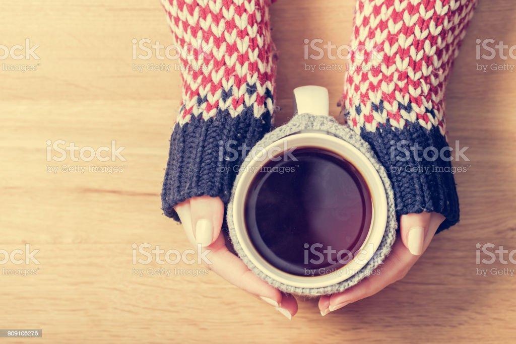 Hot mug of tea warming woman's hands in retro jumper. stock photo