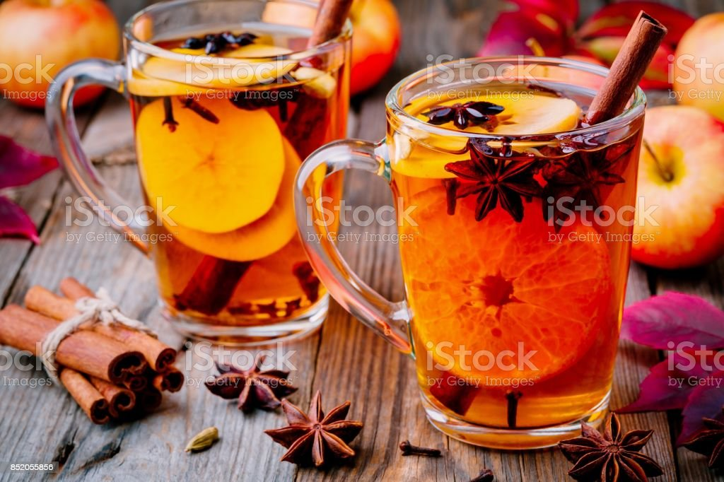 Hot mulled apple cider with cinnamon sticks, cloves and anise stock photo