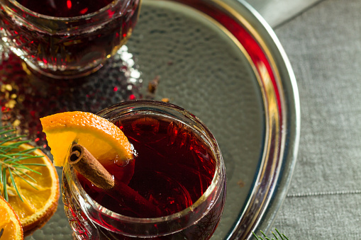 Hot mulled red wine on christmas table decorated by orange slices, spices and spruce twigs.