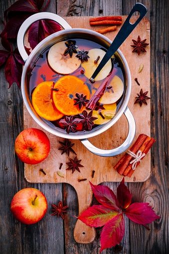 istock Hot mulled wine drink with citrus, apples, cinnamon sticks, cloves and anise in cooking pan 852056134