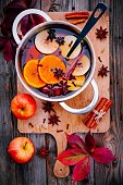 Hot mulled wine drink with citrus, apples, cinnamon sticks, cloves and anise in cooking pan on wooden background