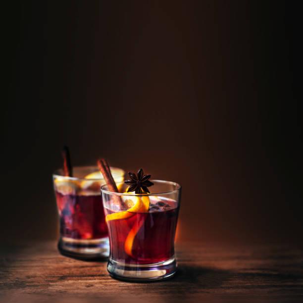 hete warme wijn voor de winter en kerstmis op houten achtergrond met copyspace.  red hot wijn met oranje groenten en specerijen - gluhwein stockfoto's en -beelden