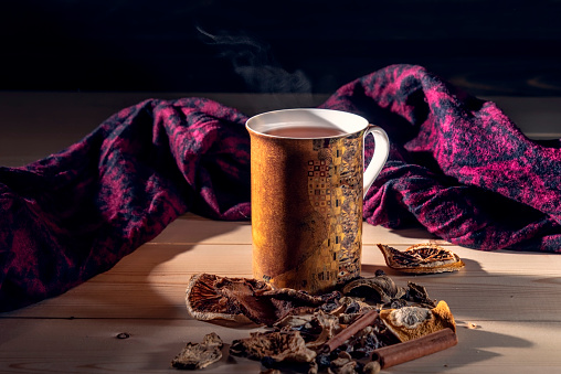 Hot mulled wine in a mug on a wooden table