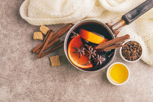 istock Hot mulled wine in a small vintage pan with ingredients on the gray slate background 1051223814