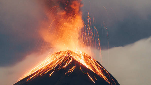 Hot orange lava coming out of fuego volcano Long exposure of the exploding crater of the volcano on the sunset volcano stock pictures, royalty-free photos & images