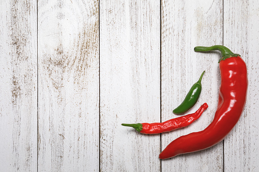 Fresh, red and green organic chili peppers on a whitewashed rustic wooden pallet with space for text