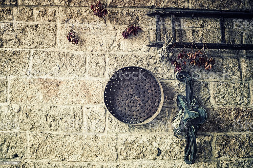 Hot peppers and old equipment hanging on the wall, Italy stock photo
