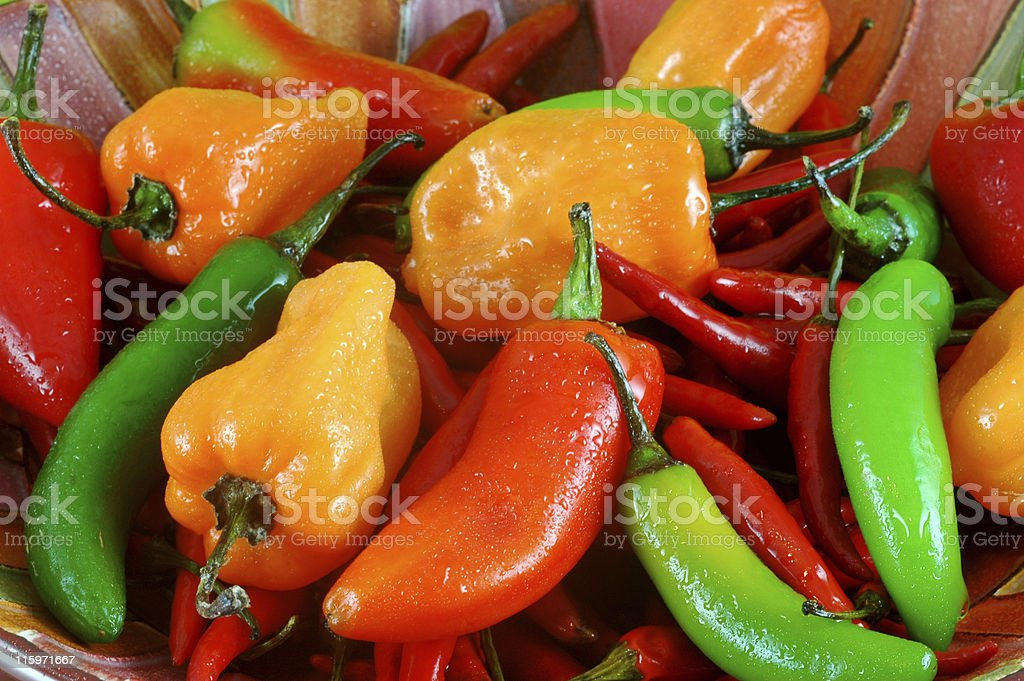 Hot peppers in various colors and types piled on each other stock photo