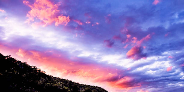 Hot pink colored cumulus cloud, sunset seascape. stock photo