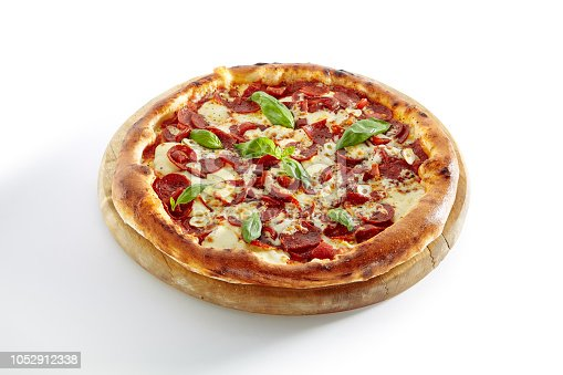 Hot Pizza Diabolo with Jalapeno Pepper, Mozzarella Cheese, Salami, Garlic, Tomato Sauce, Olive Oil and Basil Isolated on White Background. Traditional Italian Whole Flatbread on Wood Close Up