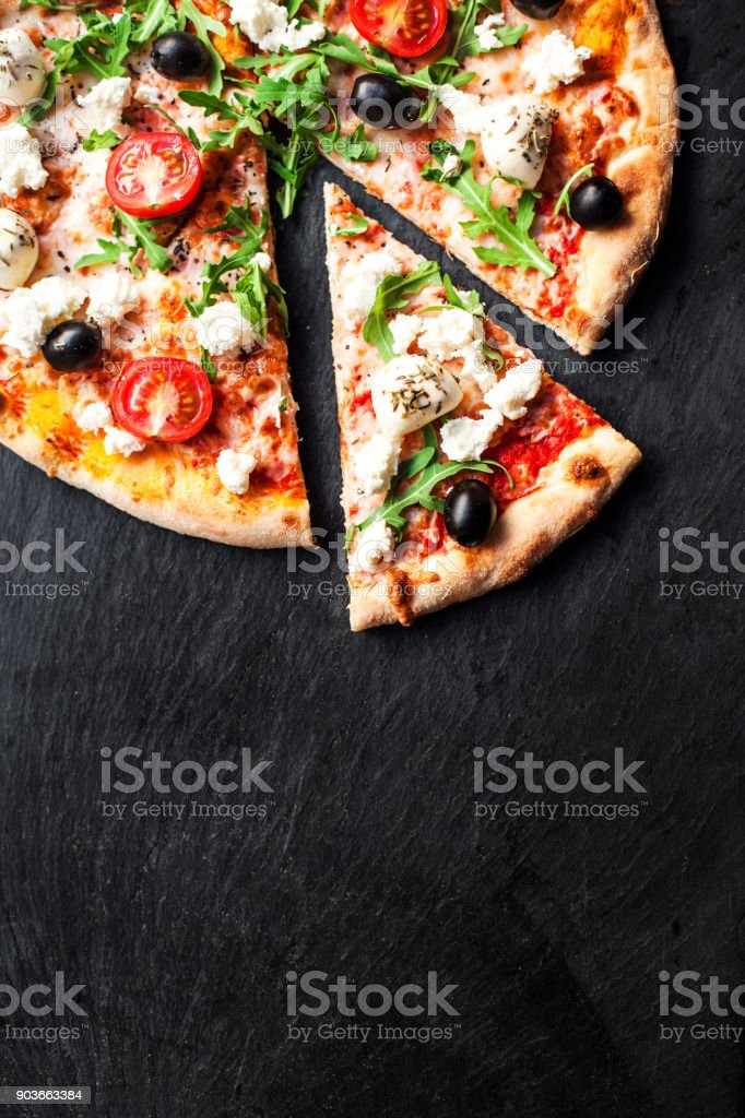 Hot pizza slice with melted mozzarella cheese and tomato on black concrete background.  Pizza Ready to Eat, Copyspace.'n stock photo