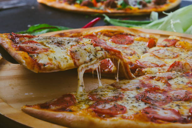 Hot pizza slice with melting cheese on a rustic dark wooden table. stock photo