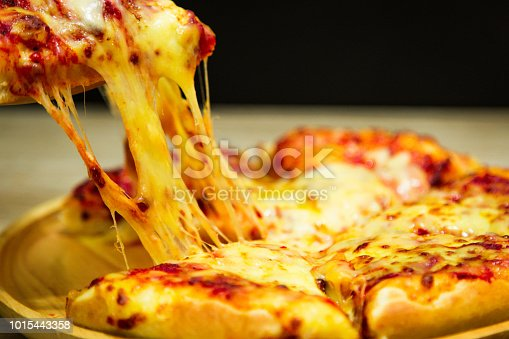 istock Hot pizza slice with melting cheese on a table in restaurant pizza Italian food. 1015443358