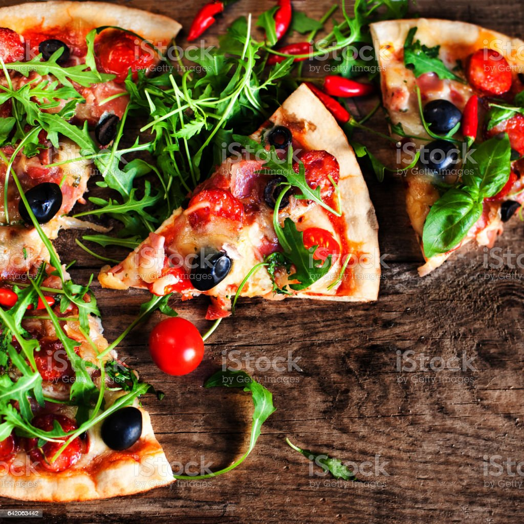 Hot pizza slice with Pepperoni, melting cheese on a rustic wooden table close up. stock photo
