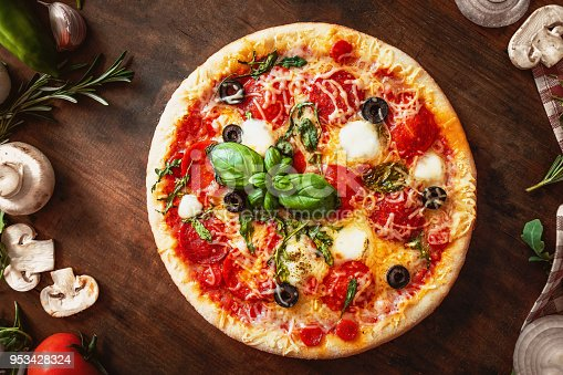 istock Hot pizza with Pepperoni  with vegetables and fresh ingredients on rustic wooden table. Pizza menu. View from above. 953428324