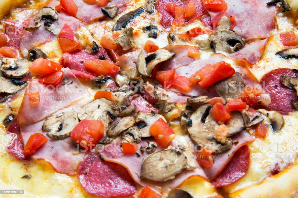 Hot pizza with tomatoes, bacon, salami, cheese and mushrooms, closeup. Side view. - Стоковые фото Бекон роялти-фри