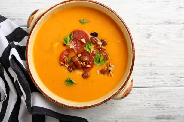 Hot pumpkin soup with chorizo and beans, food top view stock photo