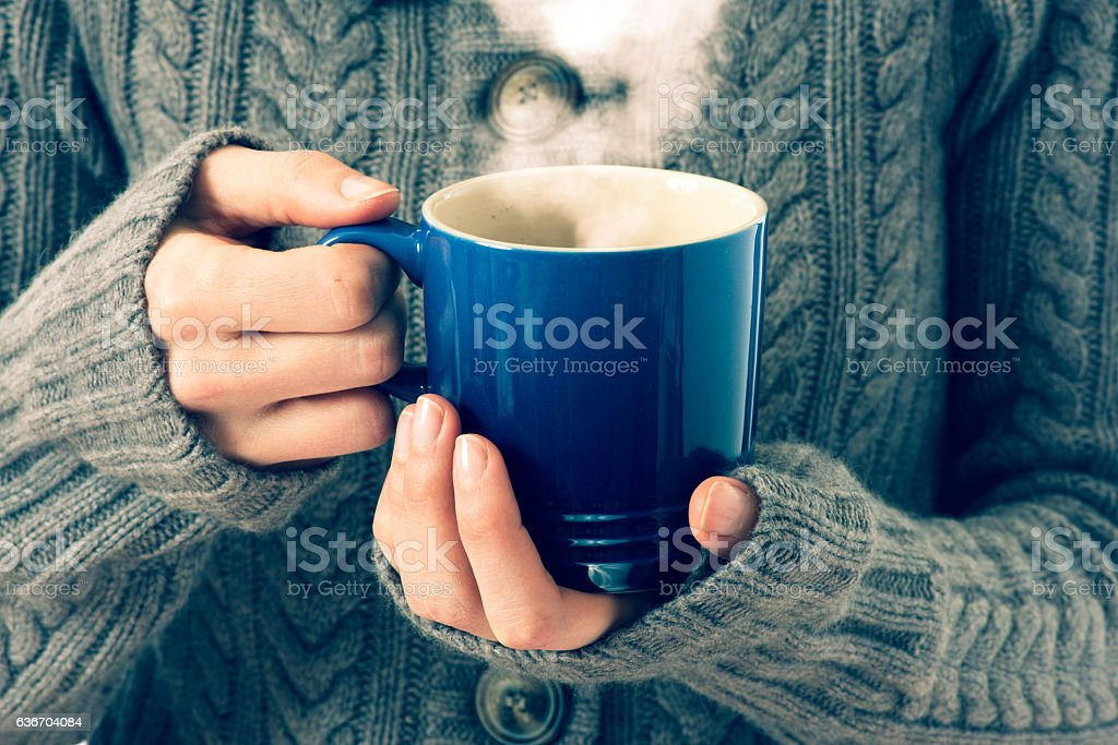 hot red cup in woman's hand, vintage colors stock photo