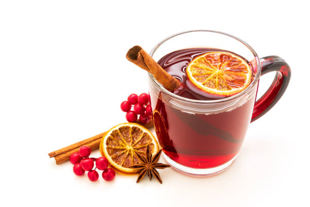 hot red mulled wine isolated on white background with christmas spices, orange slice, anise and cinnamon sticks - mulled wine stock photos and pictures