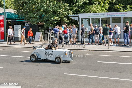 BERLIN, GERMANY - JULY 13, 2018: Unrecognized man driving a hot rod small car in downtown with predestrians on the street. Berlin is the capital and largest city of Germany by both area and population.