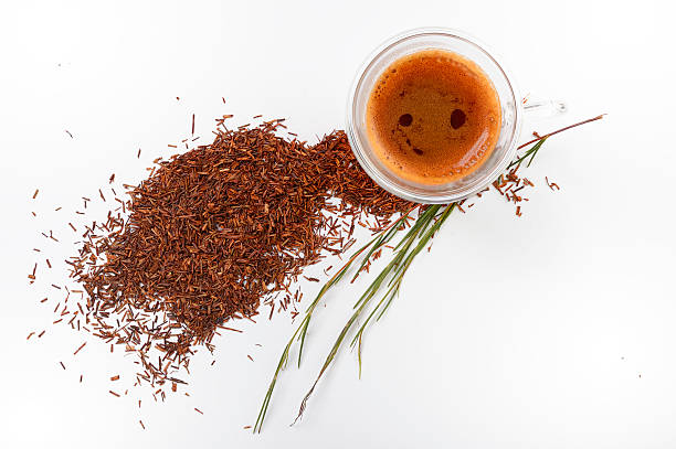 Hot rooibos espresso with fresh and cut leaves top view stock photo