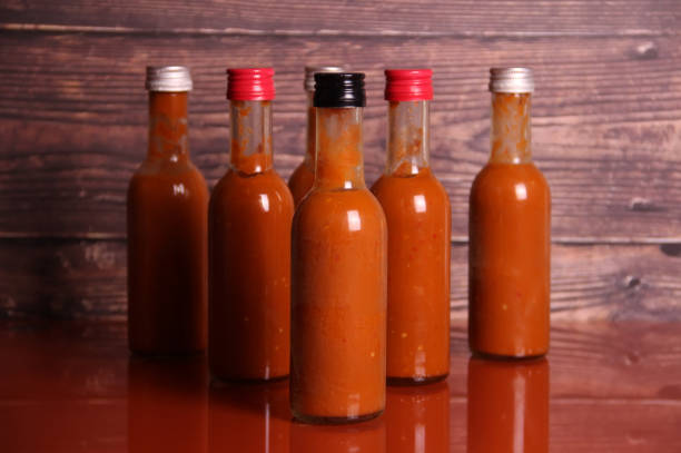 Hot sauce on a table Hot sauce on a table salsa sauce stock pictures, royalty-free photos & images