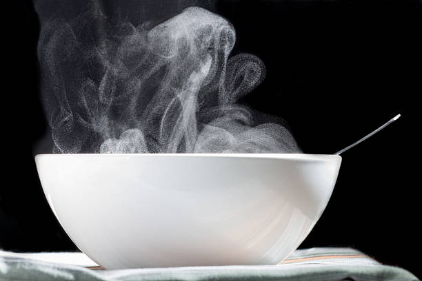 hot soup white cup with hot liquid evaporating on black background evaporation stock pictures, royalty-free photos & images