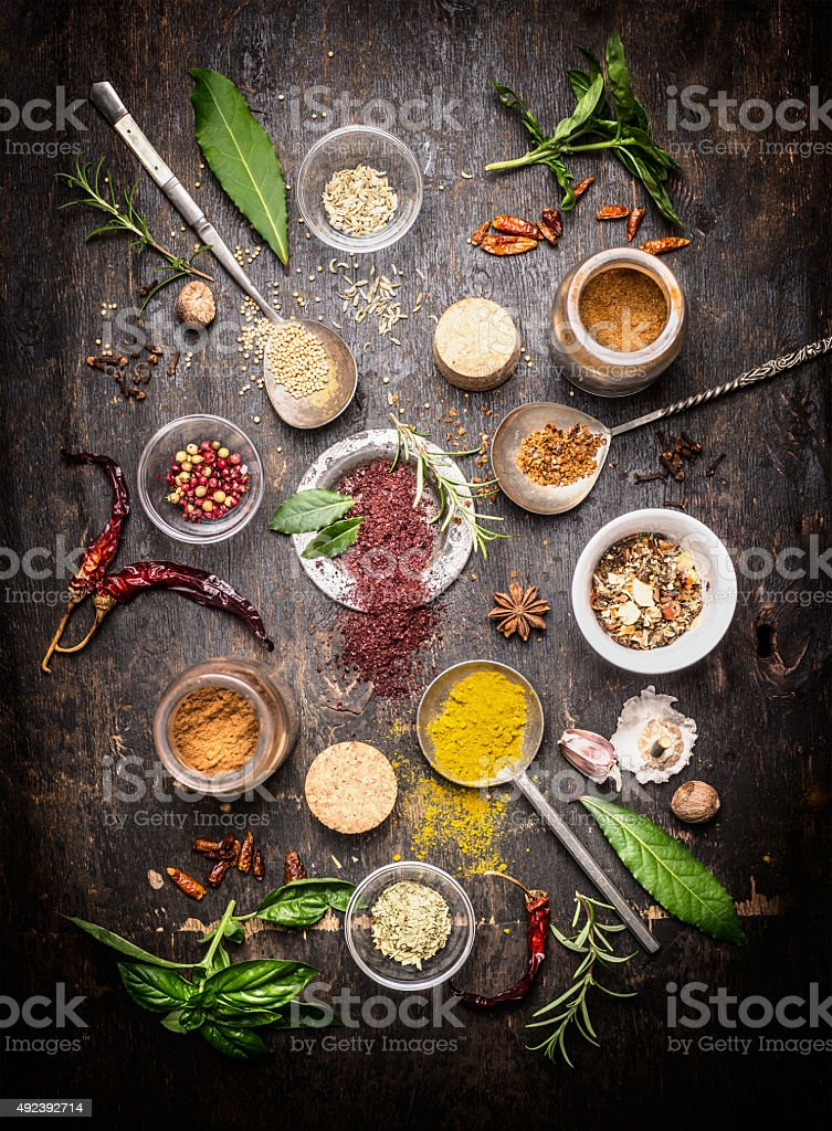 hot spices and fresh flavoring herbs on wooden background stock photo